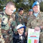 Il Generale di Brigata Luigi Francavilla insieme a un bimbo libanese protagonista della iniziativa _un disegno per la pace_, accompagnato da suo padre.